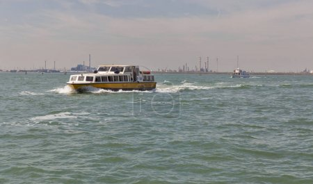 Water bus sails in Venice lagoon, Italy.