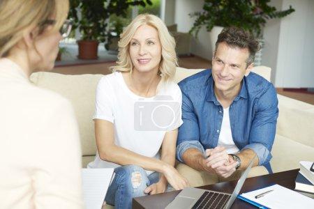 Photo pour Tir d'un couple d'âge moyen assis à la maison et la consultation avec un conseiller financier professionnel chez eux. - image libre de droit