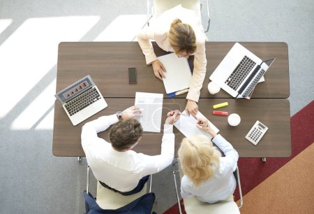 Photo for Top view shot of a business team working on new financial investment. Group of coworkers doing some paperwork while sitting desk surrounded computers. - Royalty Free Image