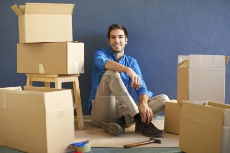 Photo for Full length shot of a happy young man sitting at  his home surrounded by cardboard boxes after moving. - Royalty Free Image