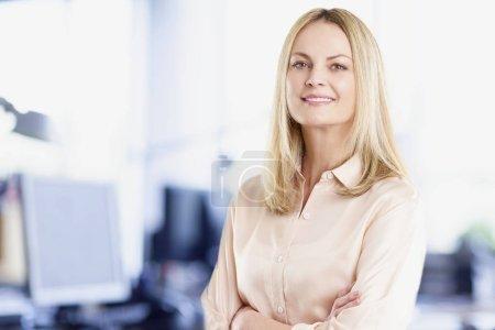 Photo pour Photo d'une femme vente confiante debout avec les bras croisés sur son lieu de travail. - image libre de droit