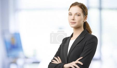 businesswoman standing  with arms crossed.