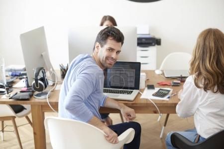 Photo pour Tir d'un jeune homme d'affaires, assis au bureau et de regarder en arrière tout en travaillant sur l'ordinateur portable au bureau avec ses collègues. - image libre de droit