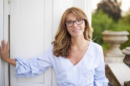 Photo for Close-up shot of a smiling middle aged woman standing on the balcony at home. - Royalty Free Image