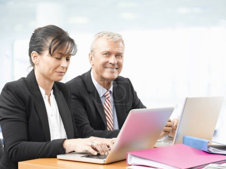 Photo pour Shot of an senior investment advisor businessman and his female financial assistant analyzing financial data while working on laptops. - image libre de droit