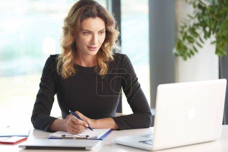 Photo pour Shot of a young female financial advisor working on laptop at desk. - image libre de droit