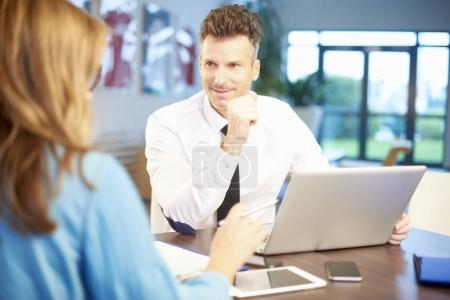 Businessman and businesswoman sitting with laptop