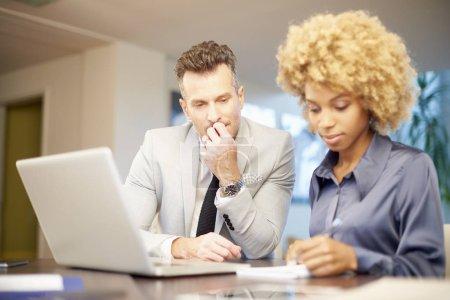 Foto de Una joven mujer de negocios haciendo un poco de papeleo mientras se sienta en el escritorio con el director financiero de mediana edad y trabajando en el ordenador portátil juntos . - Imagen libre de derechos