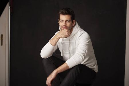 Photo pour Studio plan d'un beau jeune homme regardant pensivement tout en étant assis à fond sombre avec les mains sur son menton . - image libre de droit