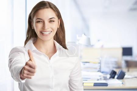 businesswoman giving thumb up while standing