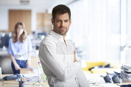 Phlegmatic young businessman with arms crossed wea...