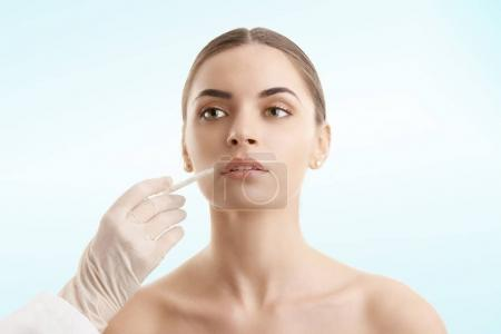 Portrait of an attractive young woman receiving lip augmentation. Isolated on light blue background.