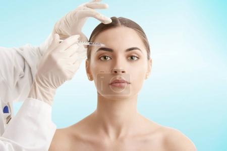 Photo pour Portrait d'une jeune femme séduisante recevant un traitement botox. Isolé sur fond bleu clair . - image libre de droit