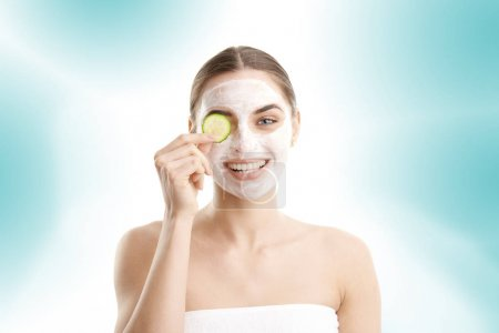Close-up portrait of a smiling beautiful young woman wearing a face mask and holding a cucumber slice in front of her eyes. Isolated on light blue background.