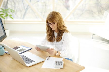 High angle shot of a financial assistant businesswoman using laptop and computer while working on new investment strategy.