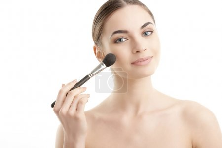 Close-up of a young woman holding brush in her hand and applying makeup. Isolated on white background.