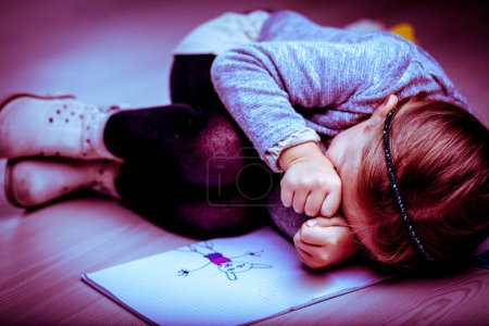 Upset little girl curled up next to her drawing