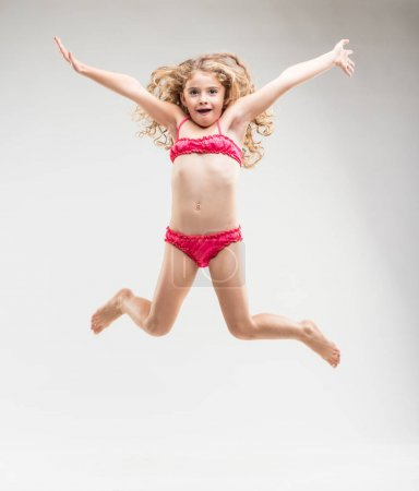 Agile exuberant little girl leaping in the air