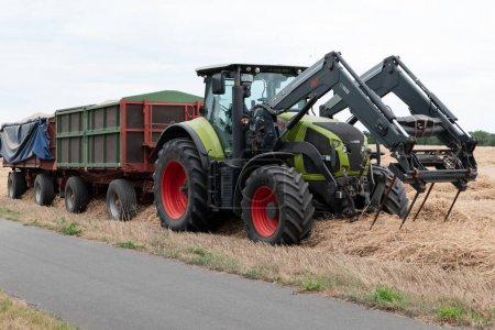 Photo pour Berlin, Berlin / Allemagne - 11.07.2019 : Un tracteur vert de Claas avec fourche à foin devant et deux remorques moissonnant et ramassant . - image libre de droit