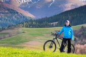 Beautiful girl, mountain biker on sunny spring day stands in a mountainous area in the green forest