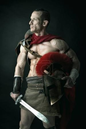Photo for Ancient warrior or Gladiator posing over a dark background - Royalty Free Image