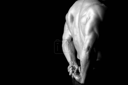 Photo for Muscled male model with strong arms and back isolated in black - Royalty Free Image