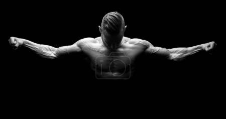 Photo for Power athletic man with open arms. Strong bodybuilder with six pack, perfect abs, shoulders, biceps, triceps and chest isolated in a black background - Royalty Free Image