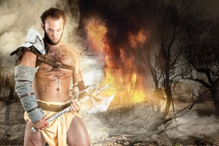 Photo for Ancient warrior or Gladiator in a burned forest with an axe - Royalty Free Image