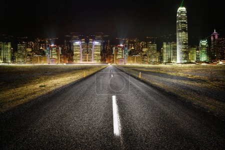 Empty road with city lights in the background