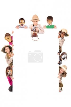 Photo for Children's group in safari clothes and animal face-paint over a white board - Royalty Free Image