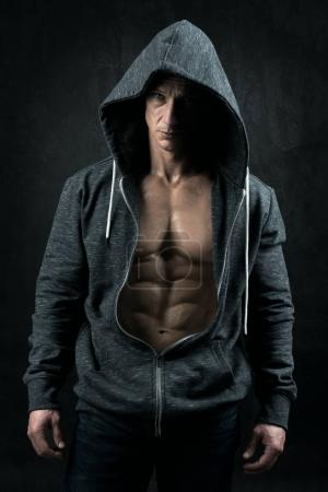 Photo for Power athletic man with hoodie showing six pack, perfect abs over a grunge background - Royalty Free Image