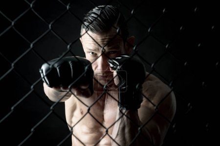 Photo for Strong Mixed Martial Arts fighter inside the cage - Royalty Free Image