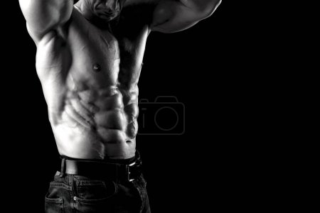 Photo for Power athletic man with great physique. Strong bodybuilder showing perfect body isolated in black. - Royalty Free Image