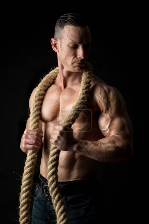 Photo for Power athletic man with great physique. Strong bodybuilder holding a big rope. - Royalty Free Image