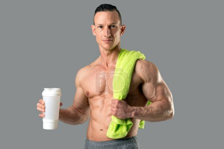 Photo for Powerful athletic man with great physique holding a gym bottle - Royalty Free Image