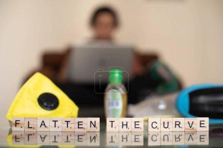 Foto de Bloques de madera con aplastamiento de la curva con un fondo fuera de foco de una joven indiana que trabaja en su portátil mientras trabaja desde casa en una cuarentena autoimpuesta en el corona covid. - Imagen libre de derechos