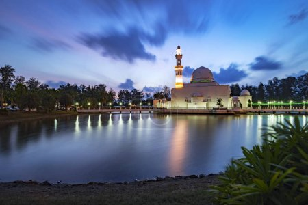 Beautiful white mosque by the lakeside during sunrise with reflection on the lake in Terengganu, Malaysia.
