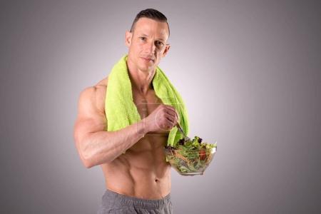 Muscular man holding salad