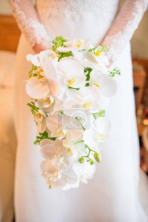 Bride holding white orchids bouquet.