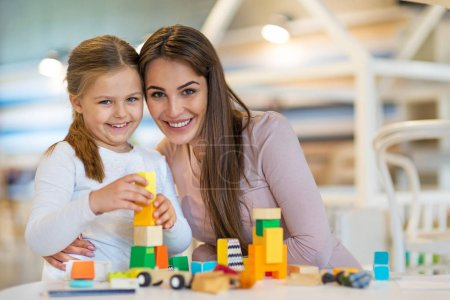 Photo for Mother and daughter playing together, smiling - Royalty Free Image