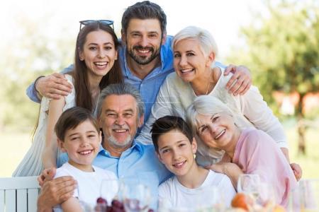 Foto de Familia sentado en la mesa al aire libre, sonriente - Imagen libre de derechos