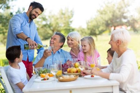 Foto de Familia sentada almorzando en el jardín - Imagen libre de derechos