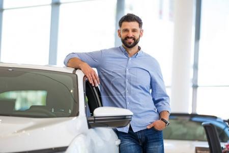 Photo pour Confiant jeune concessionnaire automobile en salle d'exposition - image libre de droit