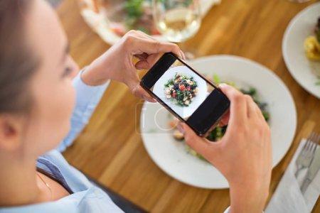 Photo pour Femme avec smartphone photographier la nourriture au café - image libre de droit