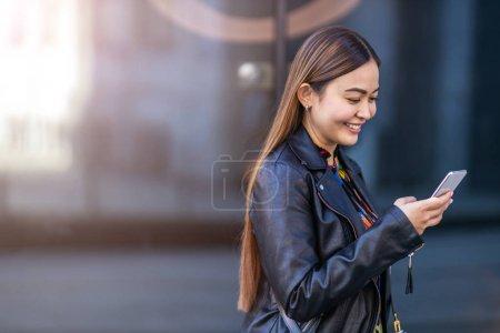 Foto de Atractiva mujer joven con teléfono inteligente y café en la ciudad. - Imagen libre de derechos