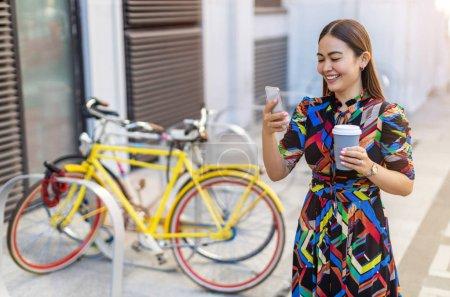 Foto de Joven hipster mujer con su bicicleta y teléfono inteligente, bebiendo café. - Imagen libre de derechos