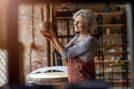 Foto de Retrato de la artista de cerámica femenina senior en su estudio de arte. - Imagen libre de derechos