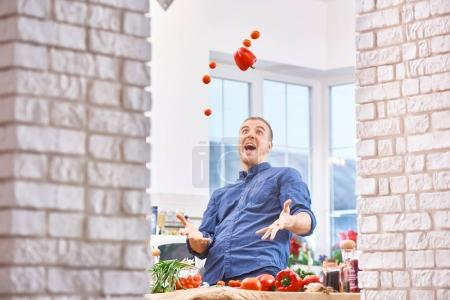 Handsome man  juggling with vegetables pepper and tomatoes