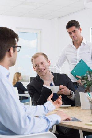 Photo pour Deux hommes élégants en regardant leur collègue de travail et souriant - image libre de droit