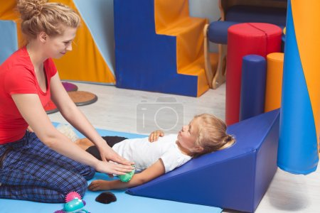 Photo for Shot of a little girl lying on the triangle pillow while therapist massaging her arm - Royalty Free Image